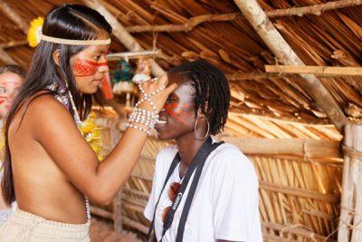 Voyageuse se faisant maquiller par une indienne lors de la visite d'un village